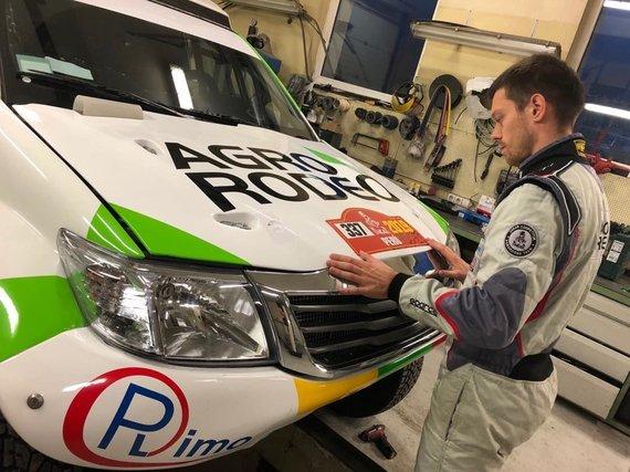Agrorodeo komandos nuotr./Vaidotas Žala klijuoja ant Agrorodeo komandos automobilio startinį Dakaro 2019 numerį