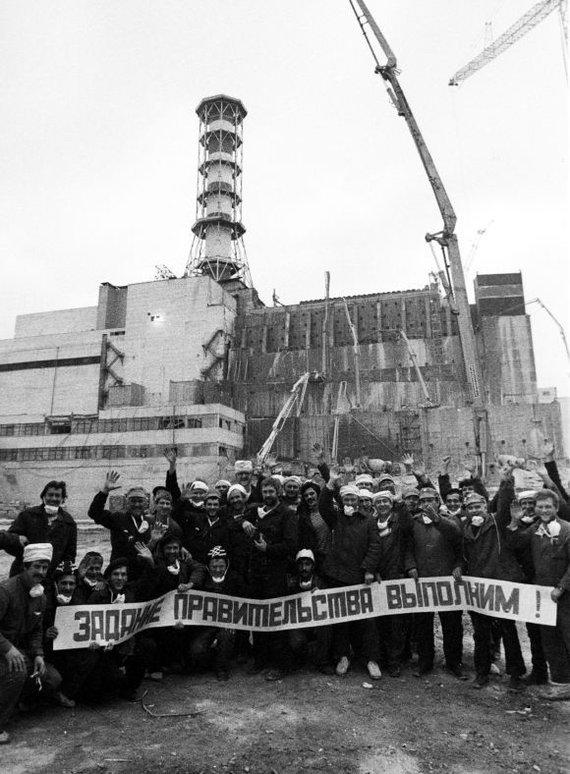 """""""Reuters""""/""""Scanpix"""" nuotr./Černobylio katastrofos likviduotojai. Ant plakato užrašas: """"Vyriausybės užduotį įvykdysime!"""""""