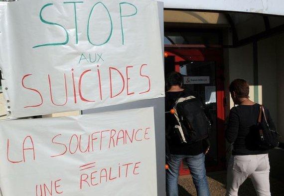 """AFP/""""Scanpix"""" nuotr./Bendrovės darbuotojai išreiškią protestą dėl įmonės veiklos, kuri priveda prie savižudybių (2009 m.)"""