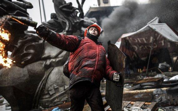 """AFP/""""Scanpix"""" nuotr./Protestuotojas meta Molotovo kokteilį."""