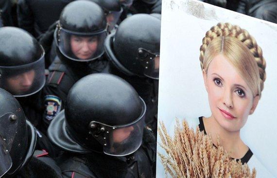 """AFP/""""Scanpix"""" nuotr./Julijos Tymošenko portretas šalia riaušių policijos pareigūnų"""