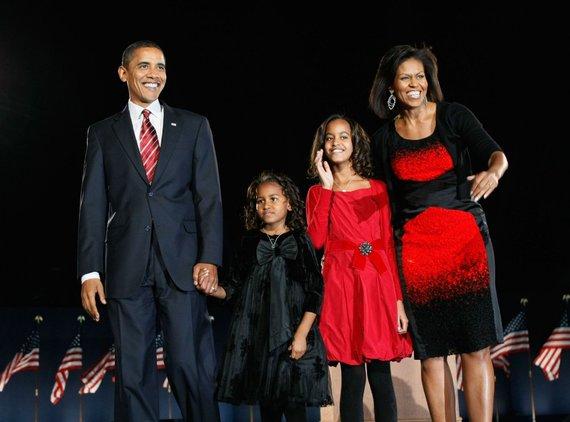 """AFP/""""Scanpix"""" nuotr./Barackas ir Michelle Obamos su dukterimis Malia ir Sasha (2008 m.)"""