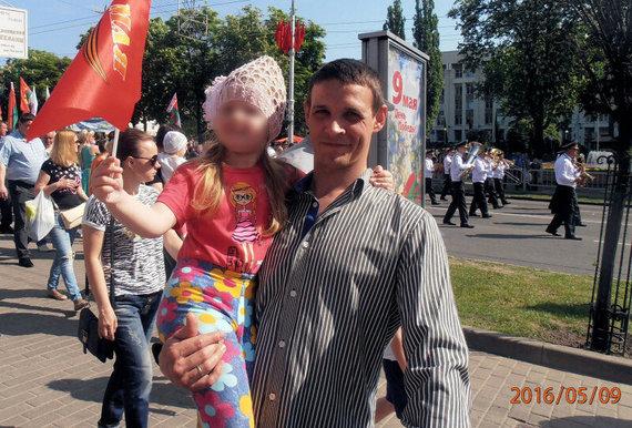 Vladimiras Didykas su dukra per šventinę eiseną Pergalės dienos garbei Sovietų gatvėje Gomelyje, 2016 m. gegužės 9 d. Fone matomi Gomelio profesinių sąjungų namai