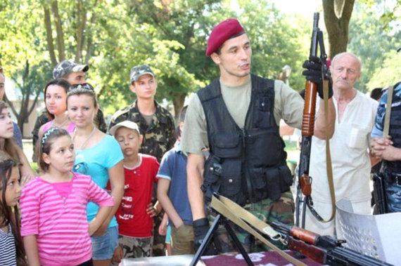 """Sergejus Kiminčiži demonstruoja """"Fort-500"""" 12-to kalibro pompinį šautuvą. Daugelis orumo revoliucijos dalyvių, įskaitant Michailą Žiznevskį, buvo nužudyti šiuo ginklu / Nuotrauka: odessitua.com"""