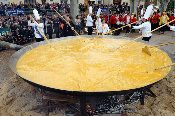 """AFP/""""Scanpix"""" nuotr./Pietų Prancūzijoje per Velykas 15 tūkst. kiaušinių yra įmušami į didžiulę keptuvę ir juos maišant kartimis iškepamas milžiniškas omletas."""