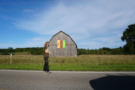 """""""Tikslas – Amerika"""" nuotr./Aistė Žemaitienė džiaugiasi Mičigano valstijoje rastais lietuviškais raštais padabintais svirnais"""