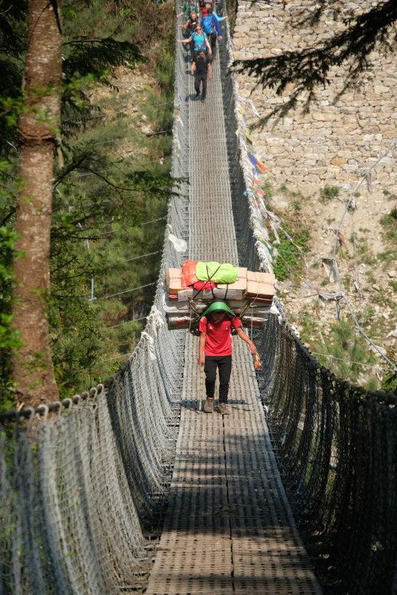 Ievos Bašarovienės nuotr./Siaurais kalnų takeliais, į stačias įkalnes, per vėjyje siūbuojančius tiltus – taip ant nešikų pečių atkeliauja ir turistams skirtas maistas bei gėrimai