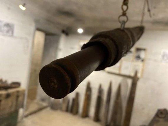Jono Valaičio/VE.LT nuotr./Įrengtame amunicijos sandėlyje pakabintas porą metrų siekiantis ištuštintas sviedinys
