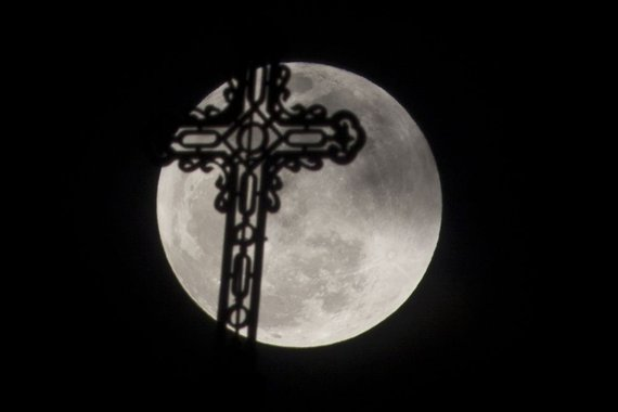 """Reuters""/""Scanpix"" nuotr./Pilnatis bažnyčios kryžiaus fone"