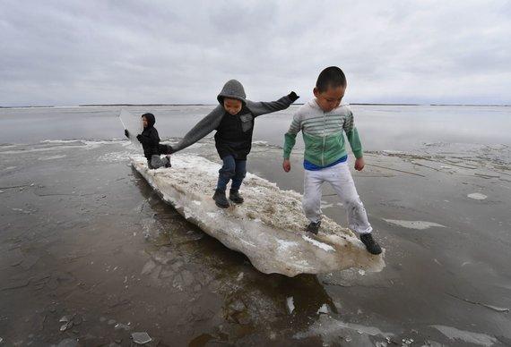 """AFP/""""Scanpix"""" nuotr./Eskimų vaikai žaidžia ant tirpstančio ledo"""