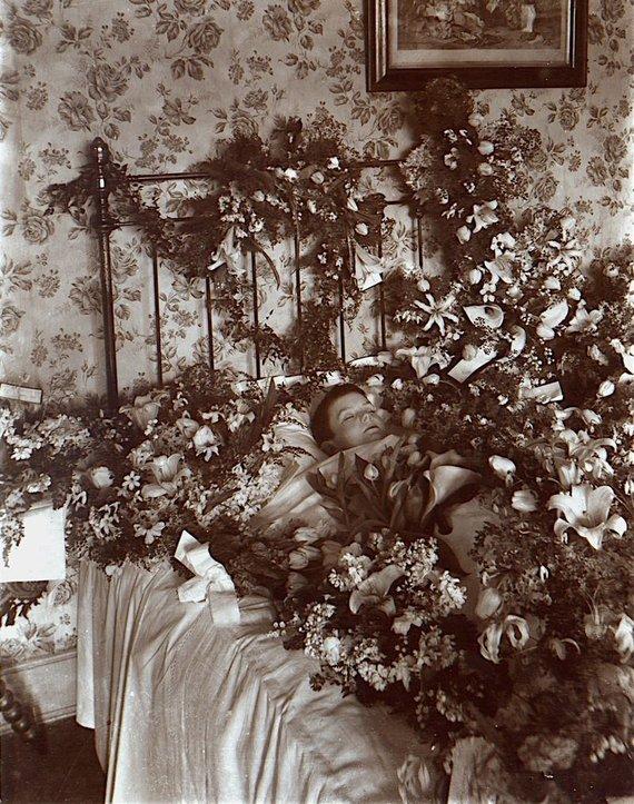 Wikimedia Commons nuotr./Miręs vaikas tarp gėlių