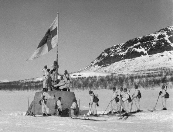 Wikimedia Commons / Public Domain nuotr./Suomijos kariai iškelia vėliavą Norvegijos, Švedijos ir Suomijos sienų susikirtimo taške karo pabaigoje