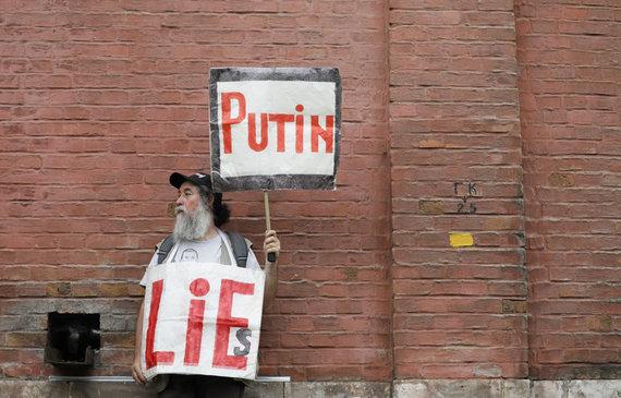 """""""Reuters""""/""""Scanpix"""" nuotr./Vienišas protestuotojas Maskvoje plakatais anglų kalba skelbia: """"Putinas meluoja"""""""