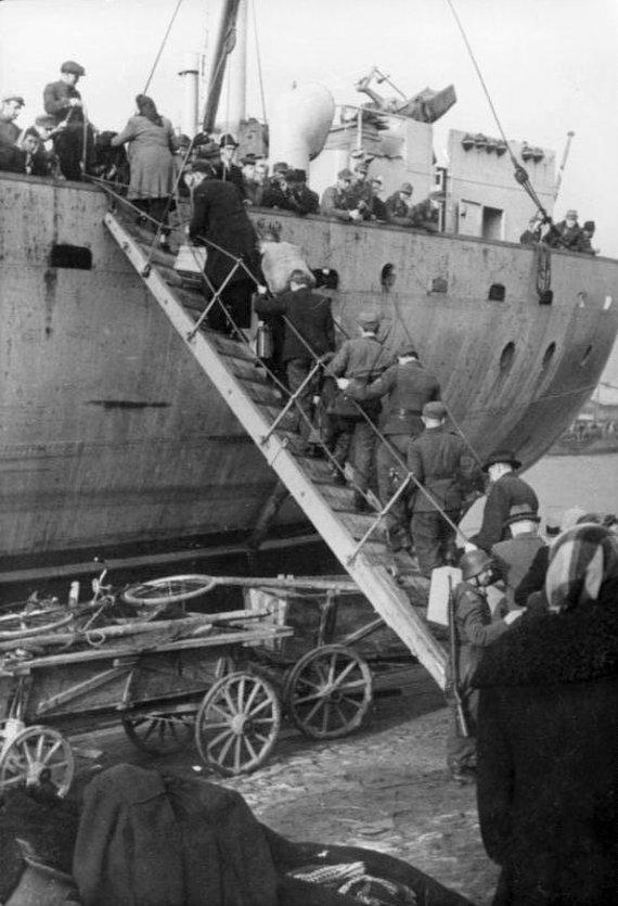 Leidyklos nuotr./Pabėgėliai ir kariai lipa į juos evakuoti turinčius laivus. Kuršas. 1944 m. spalis.