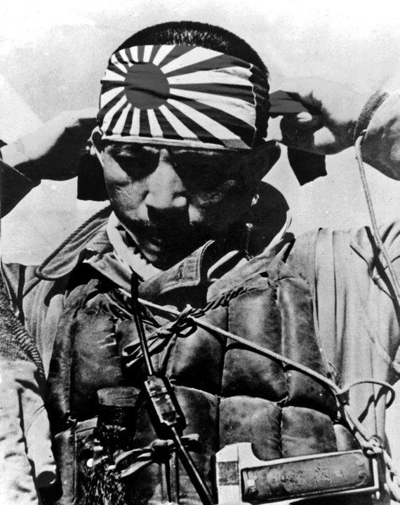 """Leidyklos """"Briedis"""" nuotr./Pilotas kamikadzė rišasi raištį su Japonijos karo vėliava – tekančios saulės piešiniu."""