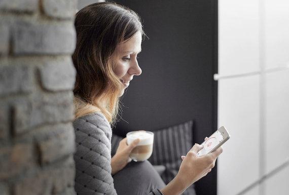 """Bendrovės """"Danfoss"""" nuotr./Moteris naudojasi išmaniąja šildymo sistema """"Danfoss Link"""""""