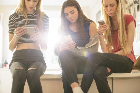 Vida Press nuotr./Paauglės naudojasi mobiliaisiais telefonais