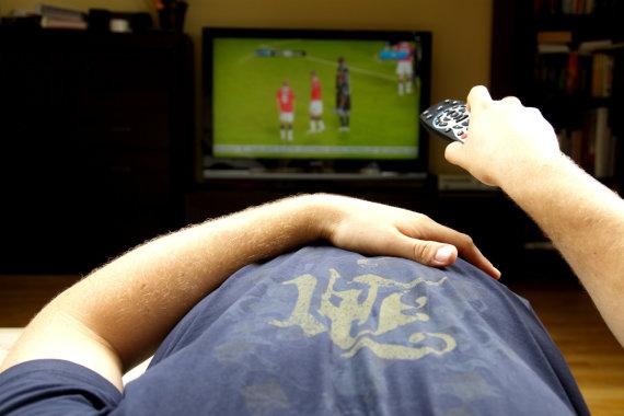 Fotolia nuotr./Užkandžiavimas žiūrint televizorių.