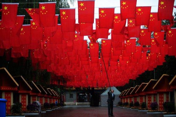 """AFP/""""Scanpix"""" nuotr./Vyras taiso Kinijos vėliavą prieš nacionalinę šventę"""