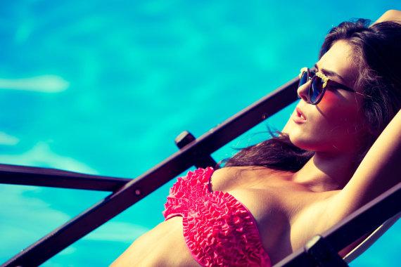 Fotolia nuotr./Moteris mėgaujasi saulės spinduliais