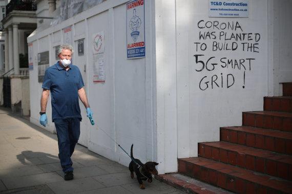 """""""Reuters""""/""""Scanpix"""" nuotr./Vyras Londone greta sienos su užrašu skelbiančiu esą COVID-19 pandemija buvo pradėta 5G ryšio tinklui išplėsti"""