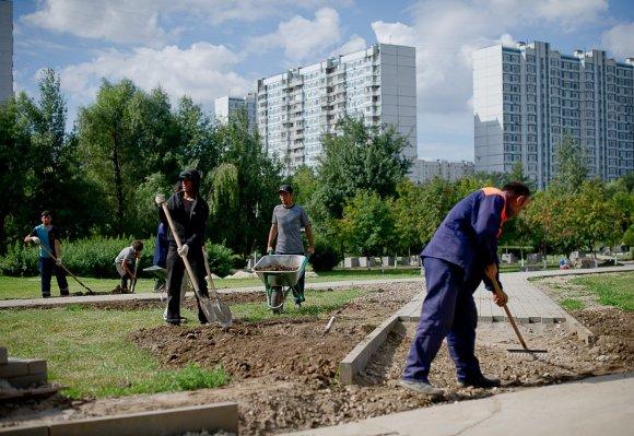 """""""Scanpix""""/""""RIA Novosti"""" nuotr./Imigrantai dirba viename iš Maskvos rajonų"""