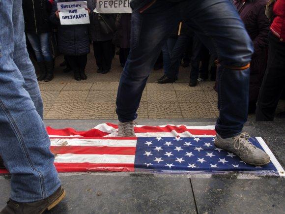 """""""Scanpix""""/AP nuotr./Protestuotojas Rusijoje trypia JAV vėliavą"""