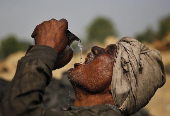 """Scanpix""/AP nuotr./Darbininkas Indijoje geria vandenį"
