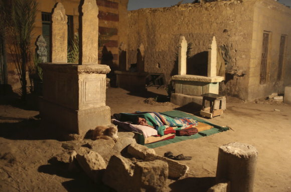 """""""Reuters""""/""""Scanpix"""" nuotr./Tvankią naktį žmogus miega lauke, greta savo namelio ir antkapių."""