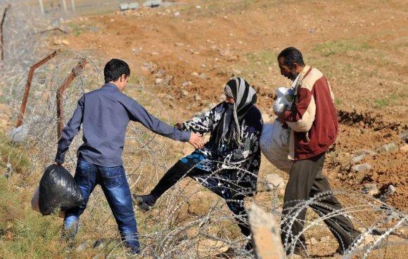 """AFP/""""Scanpix"""" nuotr./Sirijos gyventojai kerta Turkijos sieną"""