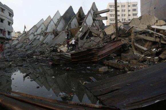 """AFP/""""Scanpix"""" nuotr./Gazos Ruože žmonės prie pastato griuvėsių"""