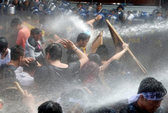 """""""Reuters""""/""""Scanpix"""" nuotr./Prieš D.Trumpą nusiteikę protestuotojai Maniloje išvaikyti vandens patrankomis"""