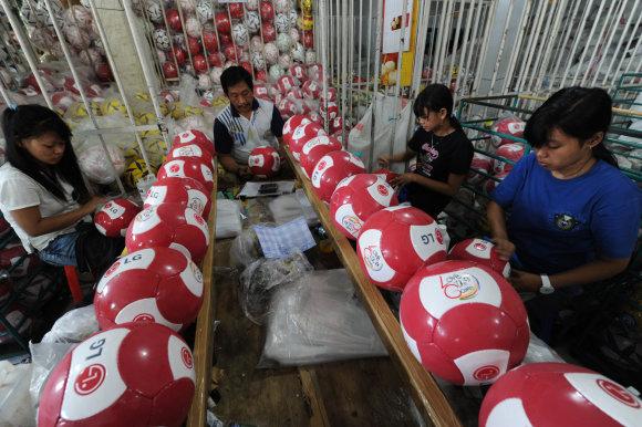 """AFP/""""Scanpix"""" nuotr./Futbolo kamuolių siuvimas"""