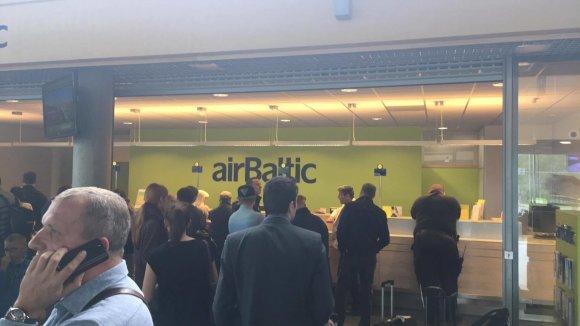 """""""AirBaltic"""" keleiviai laukia eilėje Rygos tarptautiniame oro uoste"""
