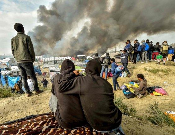 """AFP/""""Scanpix"""" nuotr./Migrantai stebi gaisrą Kalė stovykloje"""