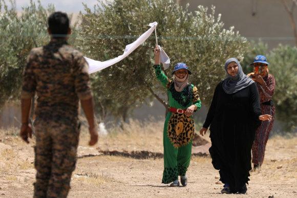 """""""Reuters""""/""""Scanpix"""" nuotr./Civiliai prie Rakos karius pasitiko mojuodami baltomis vėliavomis"""