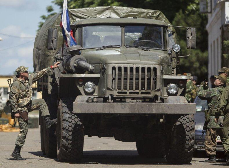 Prorusiški teroristai prie karinio sunkvežimio su Rusijos vėliava.