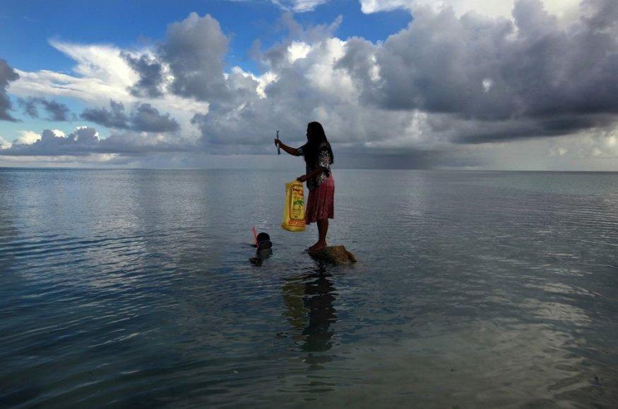 Ant akmens stovi moteris, kuri laiko vyro sugautą žuvį.