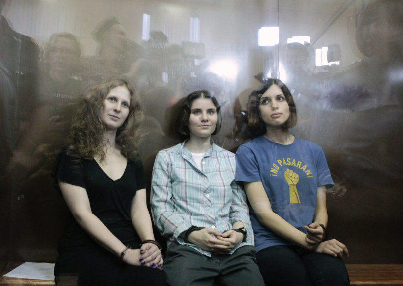 "Members of the female punk band ""Pussy Riot"" (R-L) Nadezhda Tolokonnikova, Yekaterina Samutsevich and Maria Alyokhina sit in a glass-walled cage after a court hearing in Moscow, August 17, 2012. A judge sentenced three women who staged an anti-Kremlin protest on the altar of Moscow's main Russian Or"