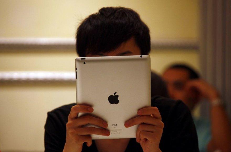 """Žmogus laiko planšetinį kompiuterį """"iPad""""."""