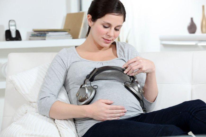 Nėščia moteris uždėjusi ausines ant pilvo