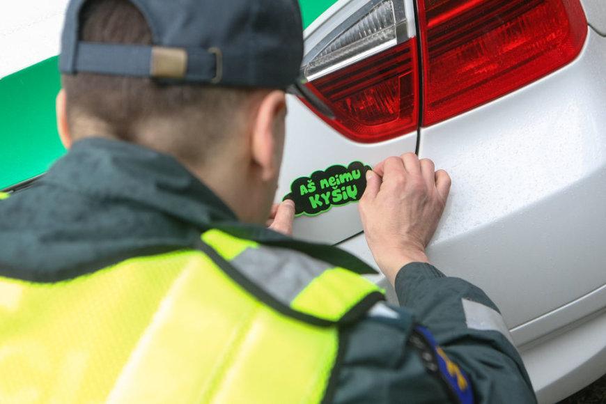 """Kelių policininkas ant automobilio klijuoja lipduką """"Aš neimu kyšio"""""""