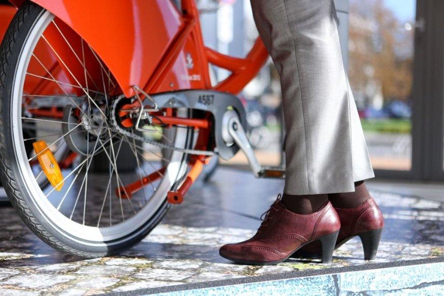 Moteris šalia dviračio