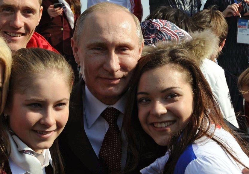 Russia's President Vladimir Putin (C) poses for a photo with figure skaters Adelina Sotnikova (R) and Julia Lipnitskaya (L) after an awarding ceremony for Russian athletes, winners of the Sochi 2014 Winter Olympics, in Sochi, on February 24, 2014. AFP PHOTO/ RIA-NOVOSTI/ POOL / MIKHAIL KLIMENTYEV