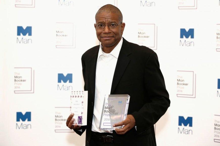 """""""Reuters""""/""""Scanpix"""" nuotr./2016 metų """"Man Booker"""" premijos laureatas Paulas Beatty laiko knygą """"The Sellout"""" ir už ją gautą apdovanojimą"""