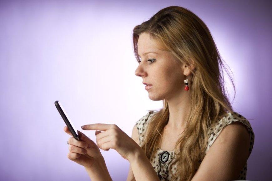 Mergina naudojasi išmaniuoju telefonu.
