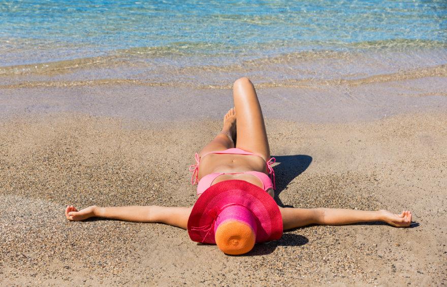 Mergina paplūdimyje deginasi.
