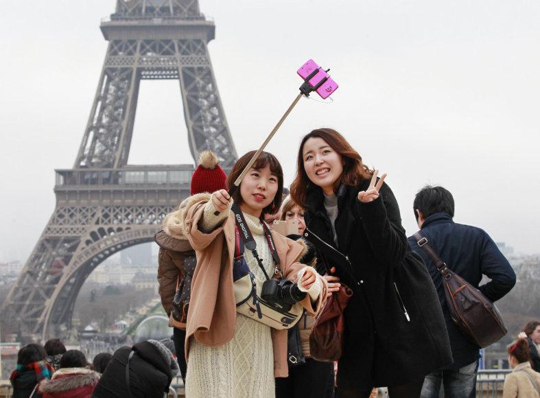 Turistės darosi asmenukę Paryžiuje prie Eifelio bokšto