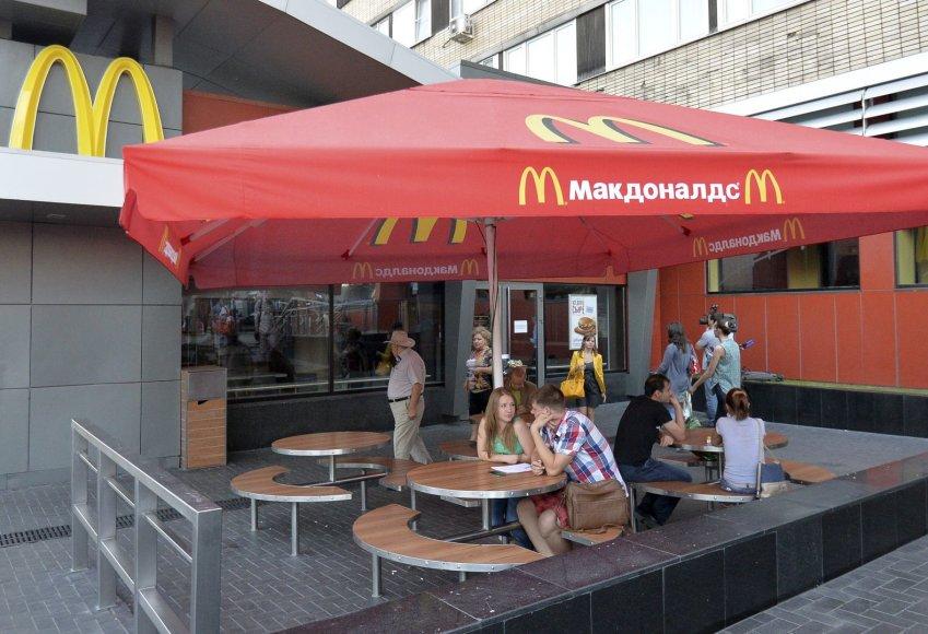 """Maskvoje žmonės sėdi prie uždaryto """"McDonald's"""" restorano stalų."""