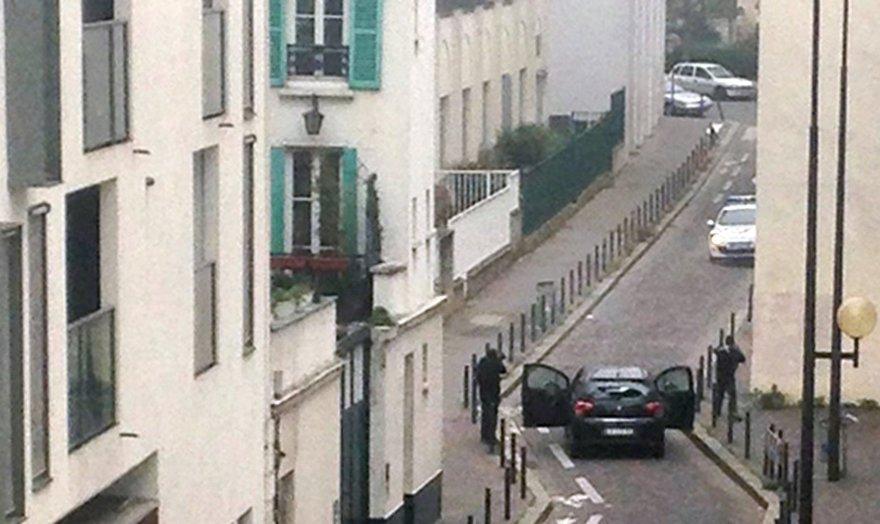 """Ginkluoti užpuolikai netoli """"Charlie Hebdo"""" redakcijos nusitaikę į policijos automobilį."""